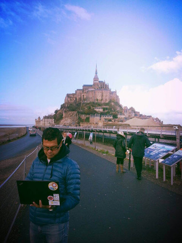 The writer checking email in front of Mont Saint Michel